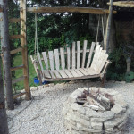 Swinging cleft chestnut chaise longue with stone firepit and circular pergola